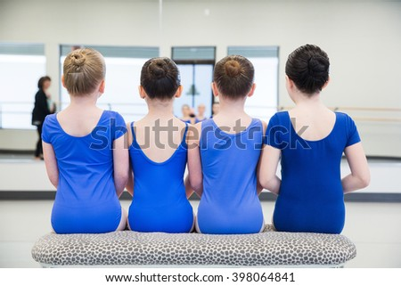 group of young girls sitting on bench - stock photo