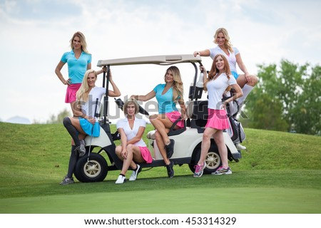 Group of young golf caddies posing on a golf cart on golf course with copy space.