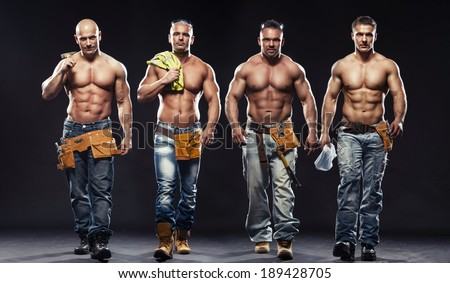 Group of young handsome builder posing, on dark background - stock photo