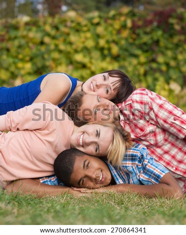 Group of young happy and smiling people lay on grass and show unity - stock photo