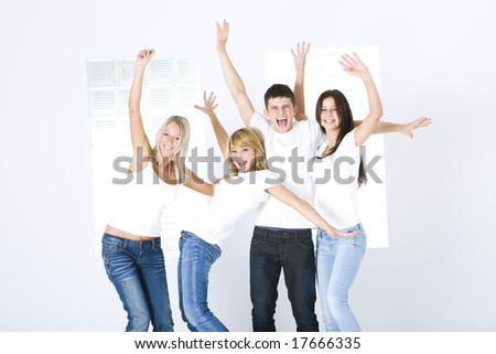 Group of young happy friends with upraised hands. They're standing and looking at camera.  Front view. - stock photo
