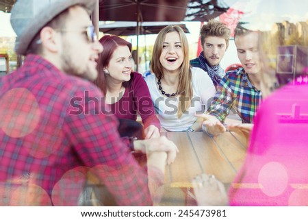 Group of young happy people enjoying and having fun (image taken behind glass reflection for desired look) - stock photo