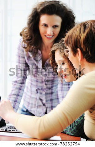 Group of young happy people looking into laptop working on it - stock photo