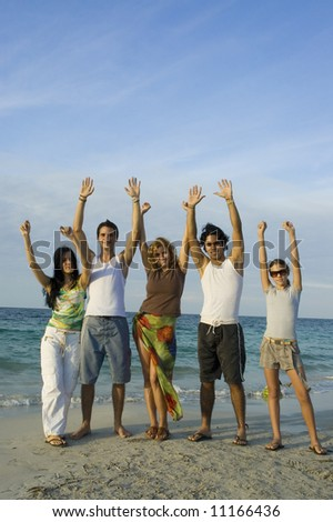 Group of young happy people on the beach with raised arms