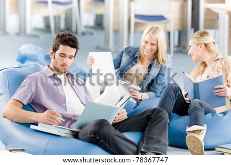 Group of young high-school students relaxing with books and laptop