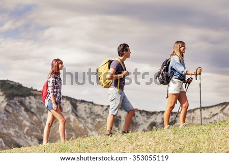 group of young hikers in the mountain in single file - stock photo