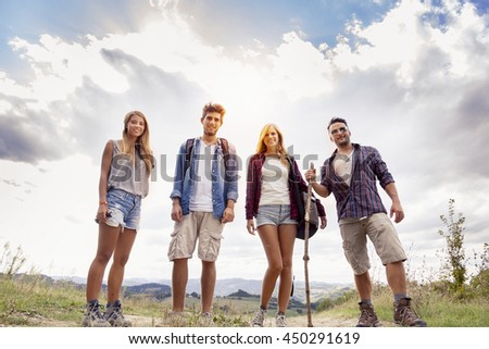 group of young hikers walking toward the horizon over the mountain - stock photo