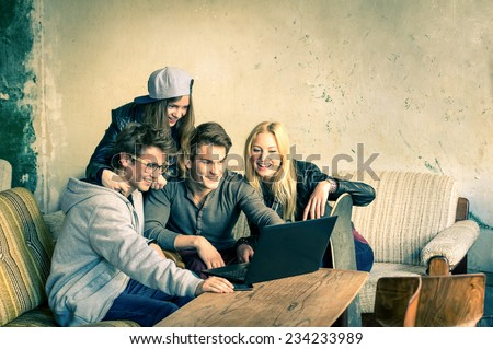 Group of young hipster best friends with computer laptop in urban alternative location - Concept of friendship and fun with new trends and technology - Wireless connection and web internet interaction - stock photo