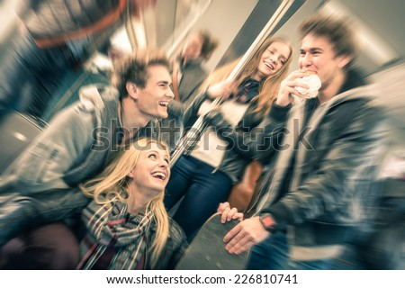 Group of young hipster friends having fun interaction and talking in subway train - Vintage filtered look with radial defocusing - Concept of youth and friendship - stock photo
