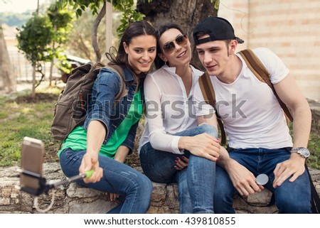 Group of young hipster friends make selfie photo with smartphone camera while traveling on vacation. Funny outdoor activity of students away from home.