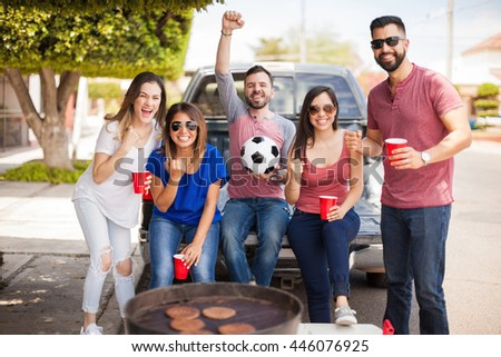 Group of young Hispanic friends celebrating their team score a goal while tailgating at a game and grilling burgers outdoors