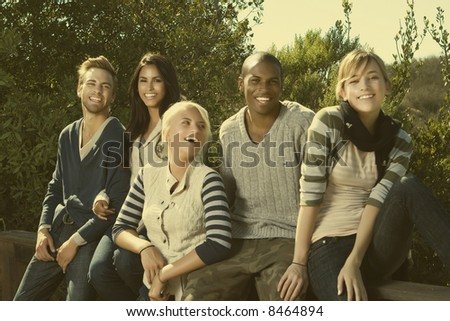 group of young interracial friends having fun in a park - stock photo