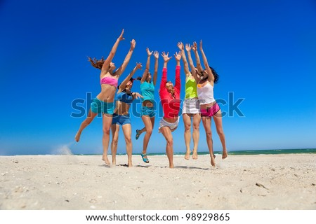 Group of young joyful girls playing on the beach - stock photo