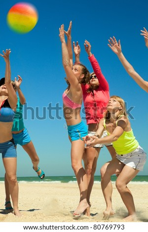 Group of young joyful girls playing volleyball on the beach