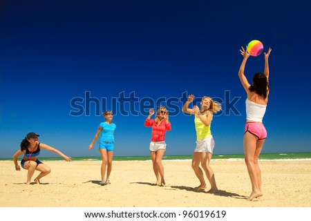 Group of young joyful girls playing volleyball, passing the ball to each other on the beach - stock photo