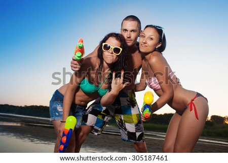 Group of young joyful young people playing and posing with water pistols on the beach  - stock photo