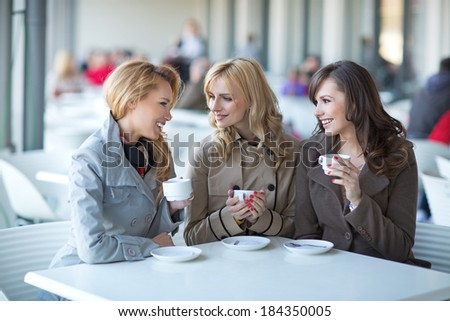 Group of young ladies drinking coffee  - stock photo