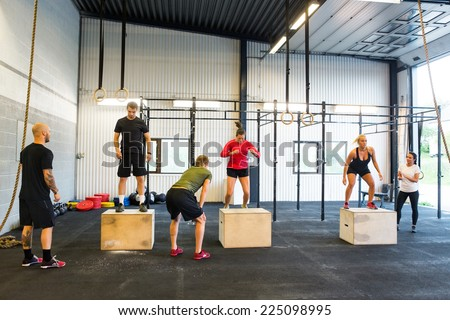 Group of young male and female athletes box jumping - stock photo