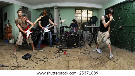 Group of young male musicians playing on messy garage - stock photo