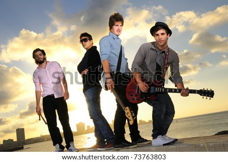Group of young male musicians posing outdoors at sunset with instruments - stock photo
