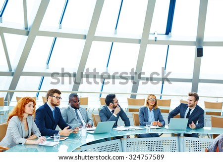 Group of young managers sitting in conference hall - stock photo