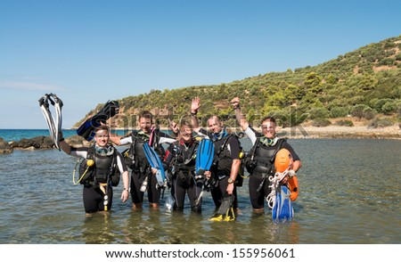 Group of young men and a female learning to dive on a Scuba Diver course - stock photo
