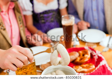 group of young men and women in traditional Bavarian Tracht having a breakfast with white veal sausage, pretzel, and beer - stock photo