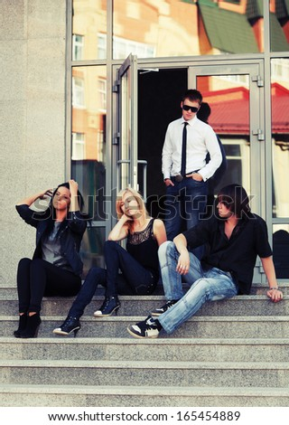 Group of young men and women relaxing on the steps - stock photo