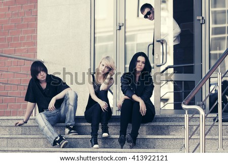 Group of young men and women sitting on the steps. Male and female fashion model