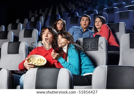 Group of young men look a terrible film at a cinema - stock photo