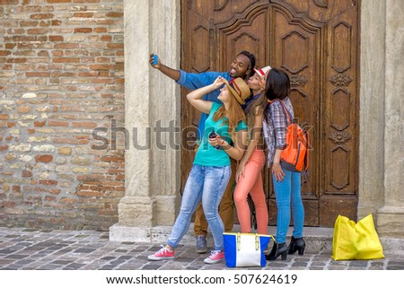 group of young multi cultural friends on a day out in an old city taking a selfie photo using smartphone - 4 people having fun taking pictures against an old wooden door