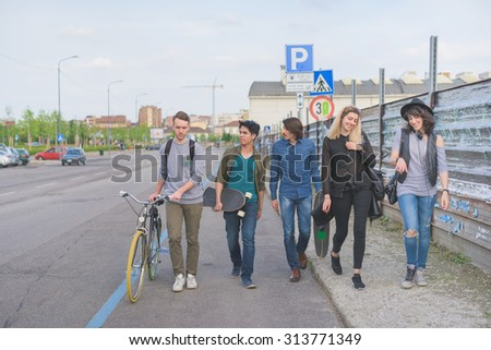 Group of young multiethnic friends walking down the street holding skateboards and bicycle, laughing and chatting each other - friendship, amusement, sportive concept - stock photo