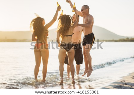 group of young multiethnic friends women and men at the beach in summer back lit drinking beer jumping and dancing - friendship, happiness, summertime concept - stock photo