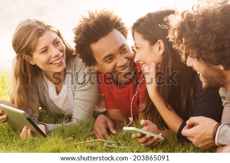 Group Of Young Multiracial People Holding Digital Tablet And Cellphone Outdoor - stock photo