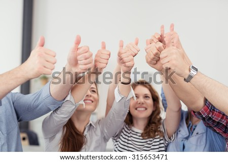 Group of Young Office Workers Showing Thumbs Up Signs Together Inside the Office. - stock photo