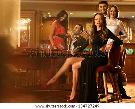 Group of young people behind table in a luxury interior  - stock photo