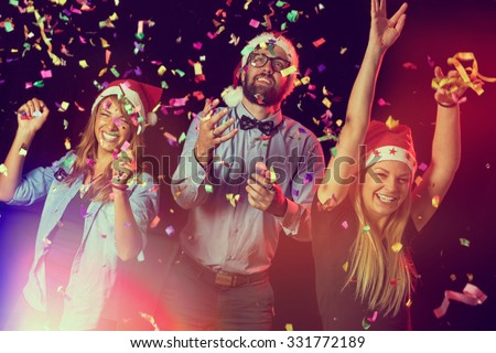 Group of young people dancing and having fun at a New Year's Eve Party - stock photo