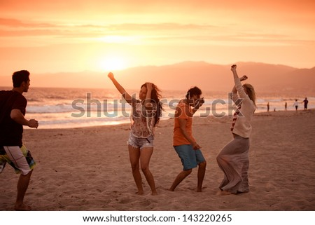 Group of young people dancing on the Beach at Sunset on 4th of July - stock photo