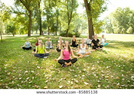 group of young people doing yoga in park - stock photo