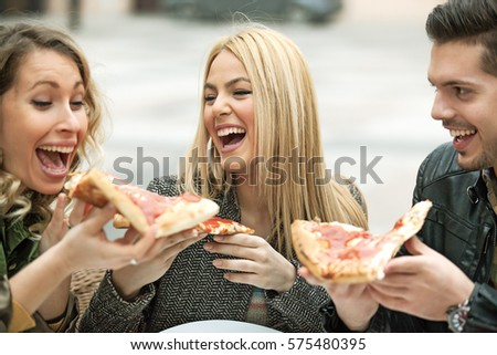 Group of young people eating pizza.