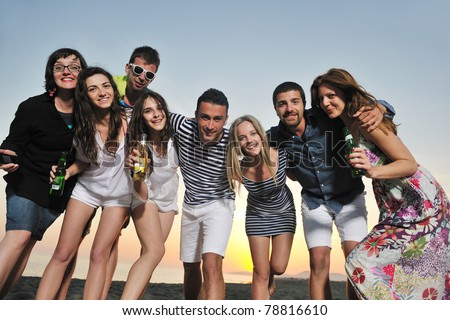 Group of young people enjoy summer  party at the beach on beautiful sunset - stock photo