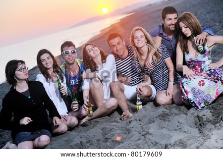 Group of young people enjoy summer  party at the beach on beautiful sunset