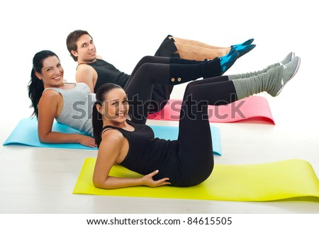 Group of young people exercising on colorful gymnastics mats in a fitness club over white background - stock photo