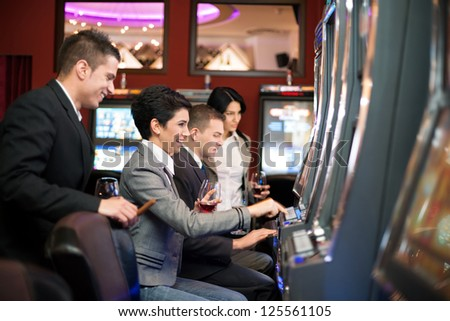 group of young people gambling in the casino on slot machines - stock photo