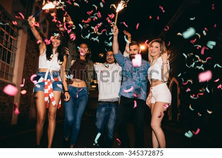 Group of young people having a party, outdoors. Multiracial young men and women celebrating with confetti. Best friend having party at night.