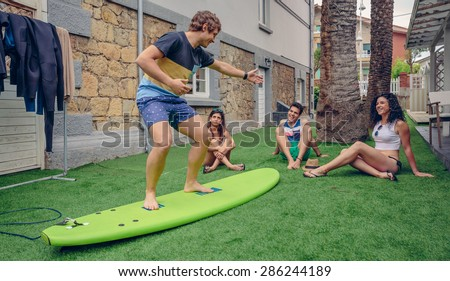 Group of young people having fun in a summer surf class outdoors. Holidays leisure concept. - stock photo