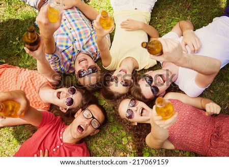 Group of young people having fun in park, lying on the grass with drinks - stock photo