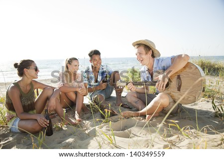 group of young people having fun on the beach - stock photo