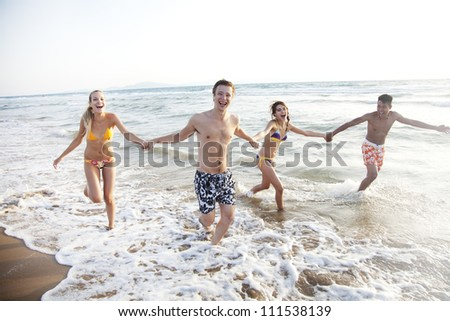group of young people having fun, running in the surf - stock photo