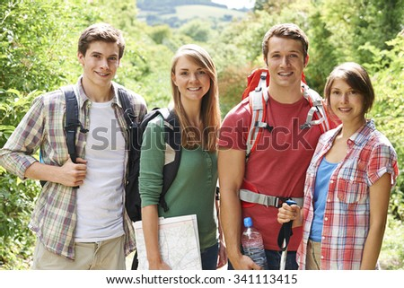 Group Of Young People Hiking In Countryside - stock photo